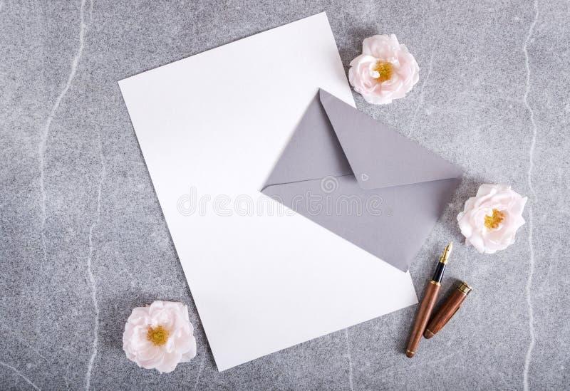 Tomt papper, grått kuvert, penna och rosor på den gråa bakgrunden Begrepp av att gifta sig inbjudanmallen fotografering för bildbyråer