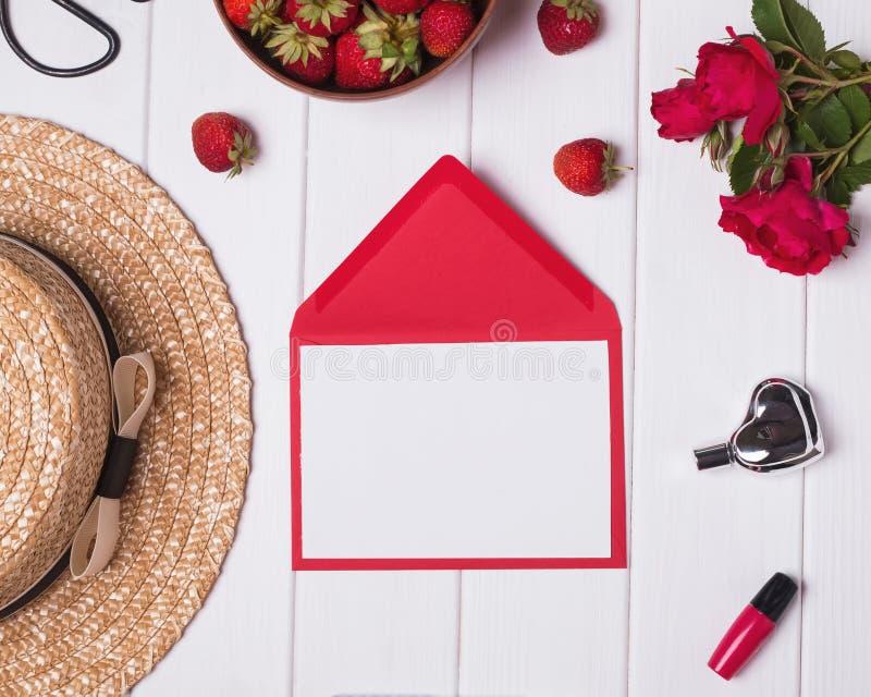 Tomt papper, hatt, röda rosor och jordgubbar på vit träbac fotografering för bildbyråer