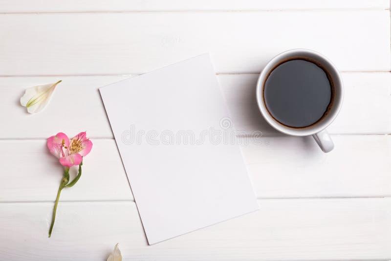 Tomt papper, kaffe och blomma på den vita tabellen arkivfoton
