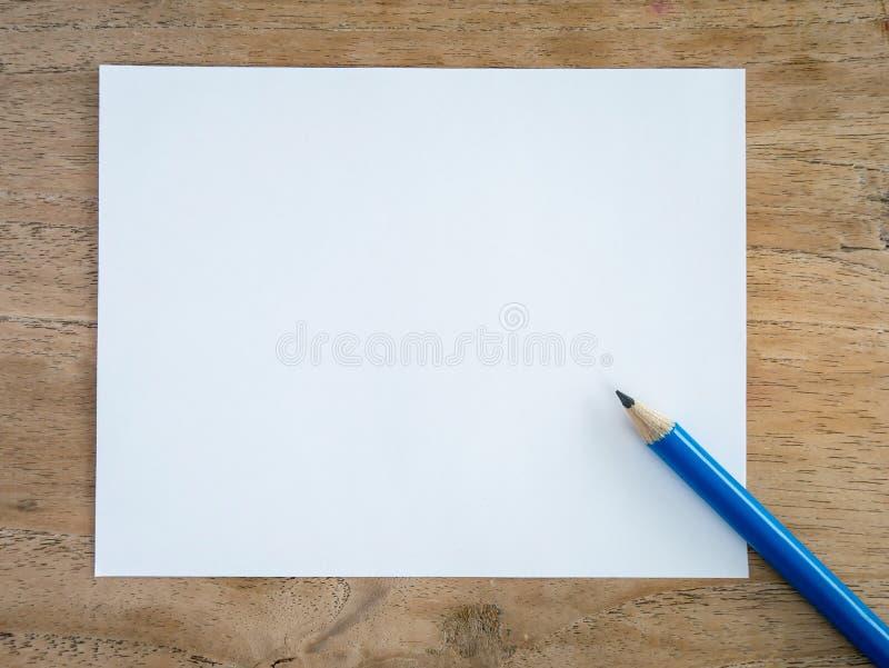 Tomt papper med blyertspennan på den wood tabellen royaltyfria bilder