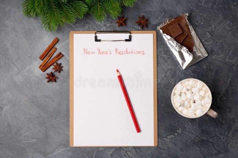 Tomt papper med det nya årets upplösningar betitlar, kaffe, stången av choklad och den röda blyertspennan på den gråa tabellen Le arkivbilder