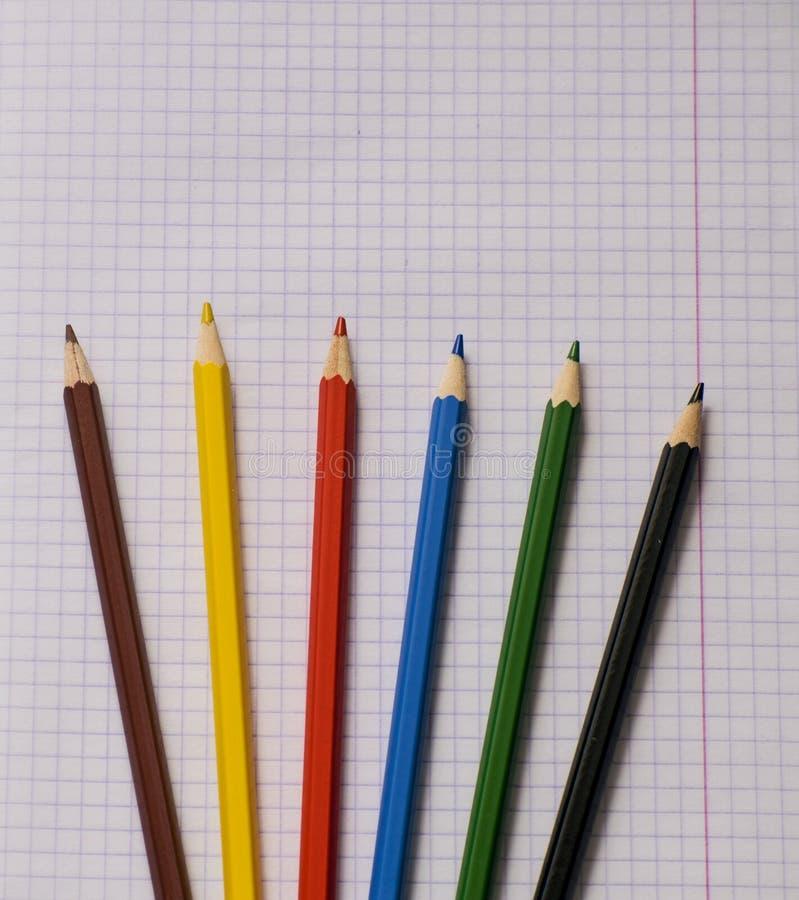 Tomt papper och färgrika blyertspennor Kulöra blyertspennor på ett anteckningsbokark Skolaanteckningsbok ovanför sikt royaltyfri bild