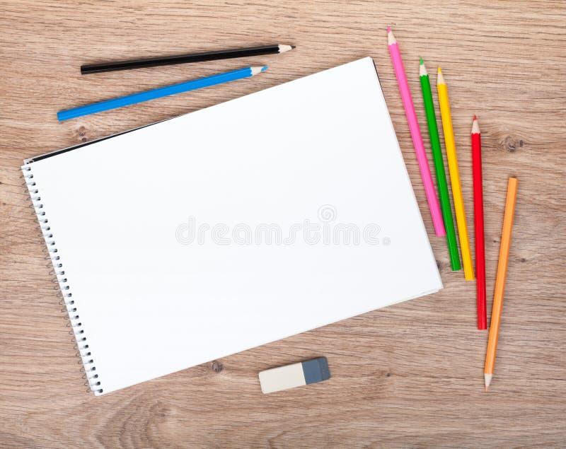 Tomt papper och färgrika blyertspennor på trätabellen royaltyfri foto