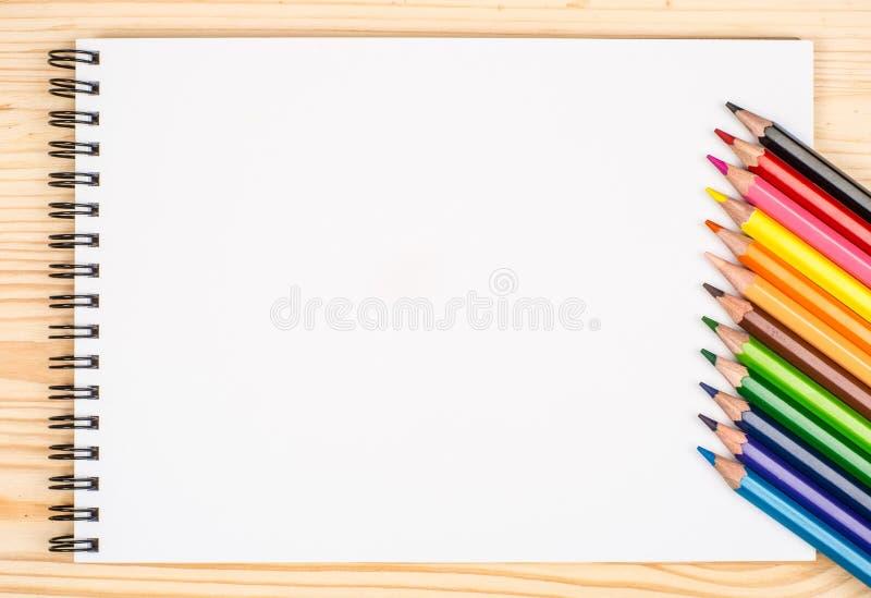 Tomt papper och färgrika blyertspennor på trätabellen royaltyfria bilder