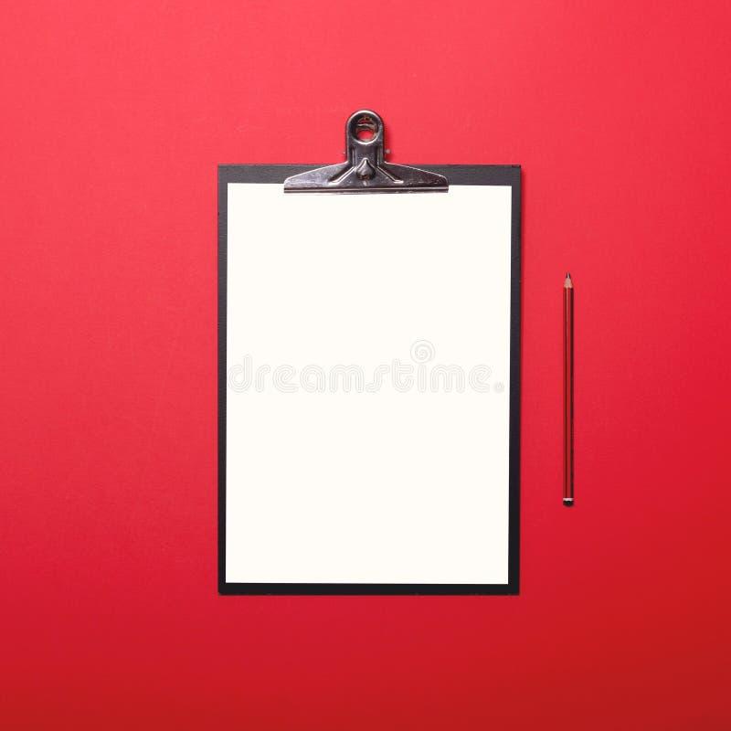 Tomt papper ombord mot röd bakgrund - bästa sikt royaltyfri fotografi
