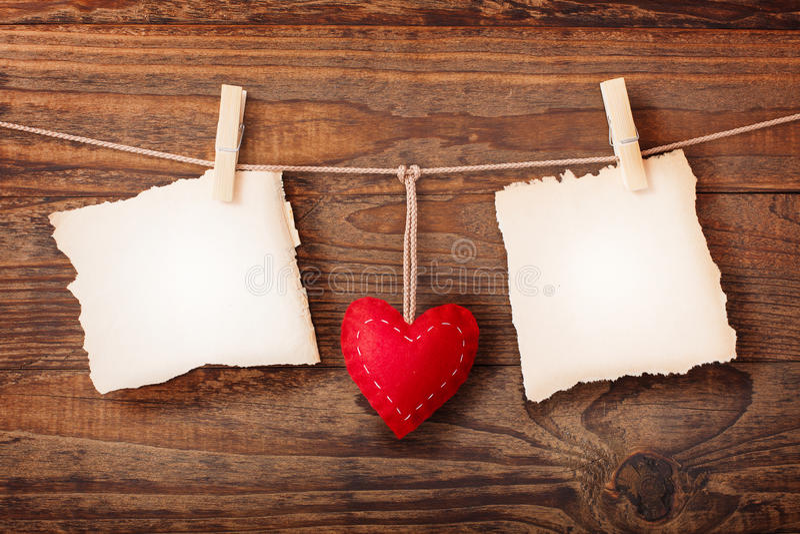 Tomt papper två och röd hjärta som hänger på träbakgrund arkivbilder
