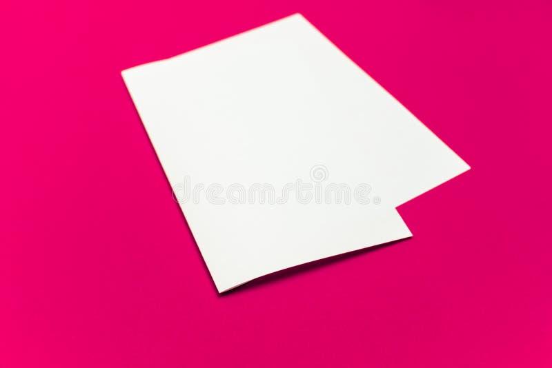 Tomt pappers- ark på 'plast- rosa färgers kulöra bakgrund royaltyfri bild