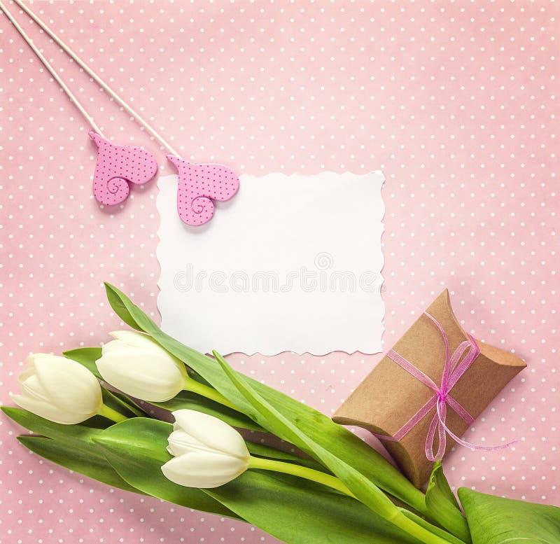 Tomt pappers- kort med den vita tulpan, hjärtor och gåvaasken på rosigt arkivbild