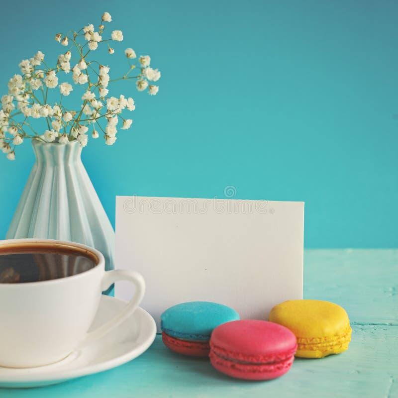 Tomt pappers- kort med kopp teandvase i blomma och makron för kvinnadag royaltyfria foton