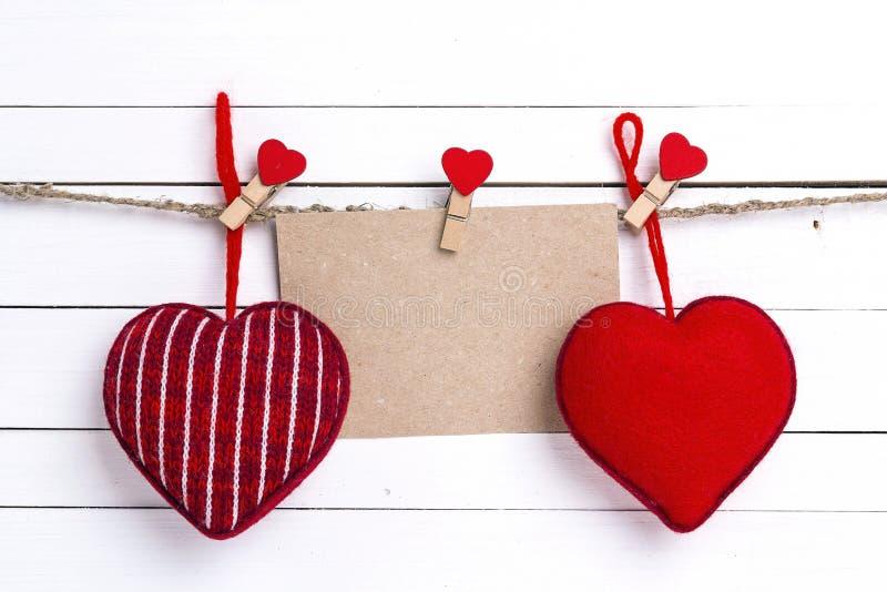 Tomt pappers- kort med röda hjärtor som hänger på klädnypor på vit royaltyfria foton