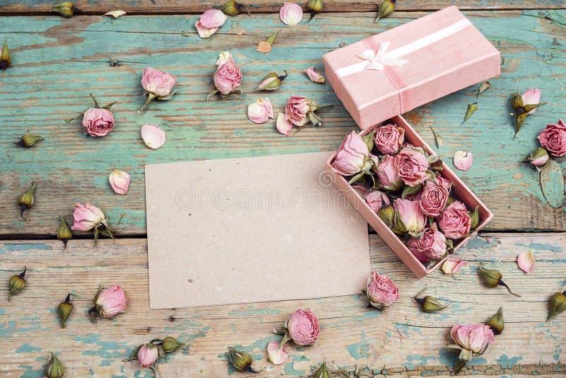 Tomt pappers- kort med små rosa rosor i en ask på gammal trät royaltyfri fotografi