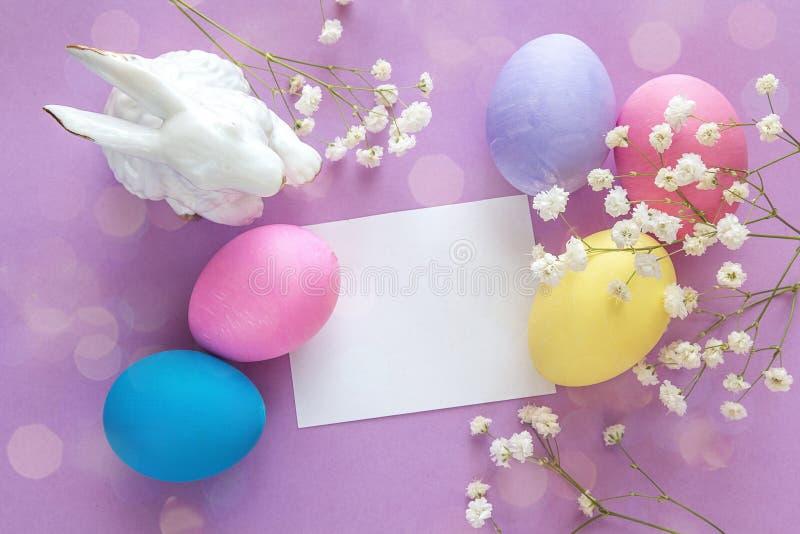 Tomt pappers- kort, påskägg, kanin och vita blommor på en pur royaltyfria foton