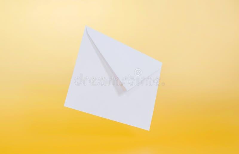Tomt pappers- kuvert på gul bakgrund arkivbild