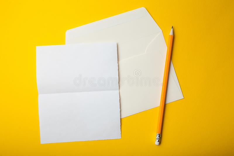 Tomt pappkort med kuvertet på gul bakgrund Modell royaltyfri foto