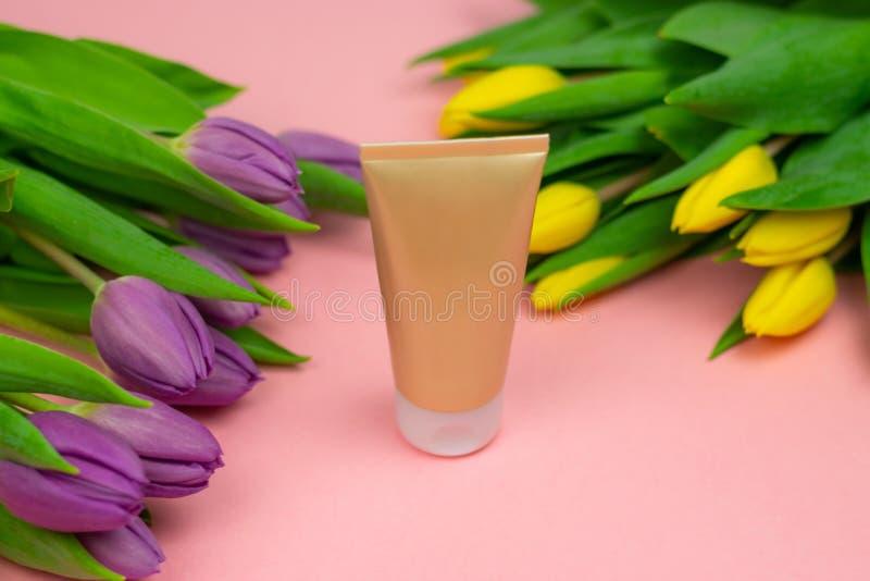 Tomt r?r av kr?m p? en rosa bakgrund med blommor arkivbilder