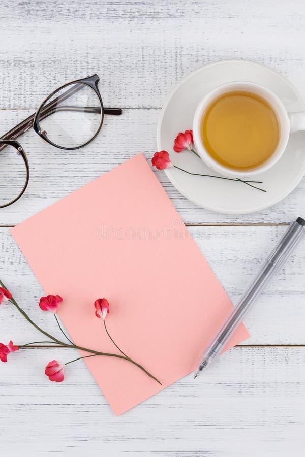 Tomt rosa kort, penna, glasögon och en kopp te royaltyfria foton