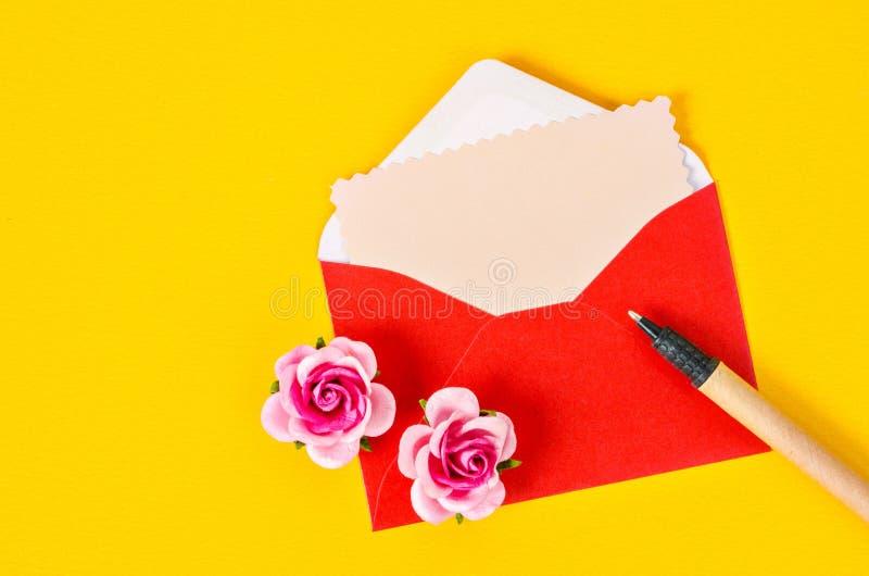 Tomt rosa pappers- kort i röd kuvertbokstav och penna royaltyfria bilder