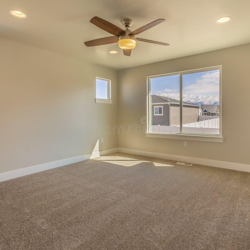 Tomt rum för fyrkantig ram av ett nytt hus med beige väggmålarfärg och det mattade golvet royaltyfria foton