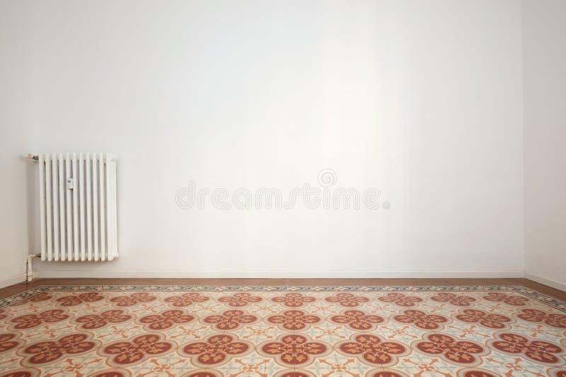 Tomt rum med den vita väggen och det belade med tegel golvet med blom- garnering royaltyfri bild