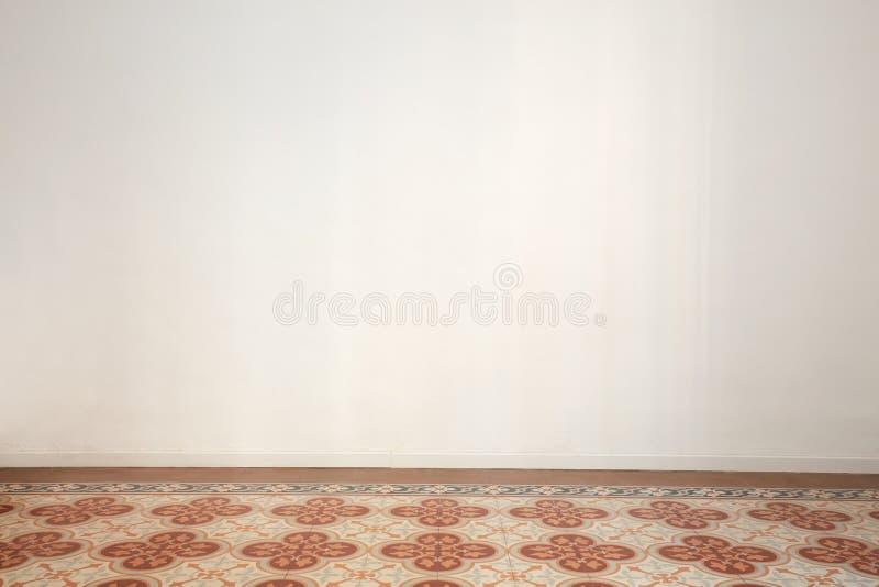 Tomt rum med den vita väggen och det forntida belade med tegel golvet i en renoverad lägenhet royaltyfri fotografi