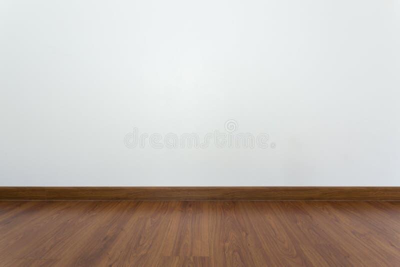 Tomt rum med det bruna wood laminatgolvet och vitmortelväggen arkivfoton
