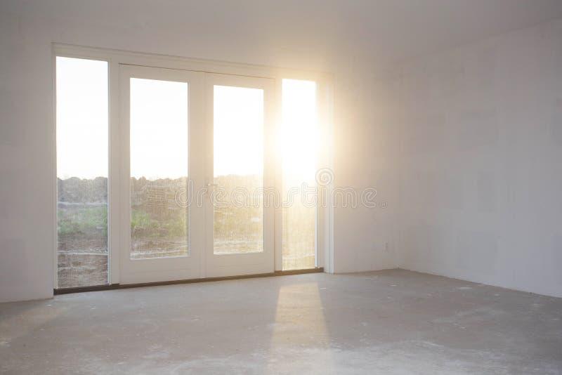 Tomt rum med det stora fönstret, ramen och dubbel doorsnewkonstruktion, fortfarande som är pågående med solljus som skiner arkivfoto
