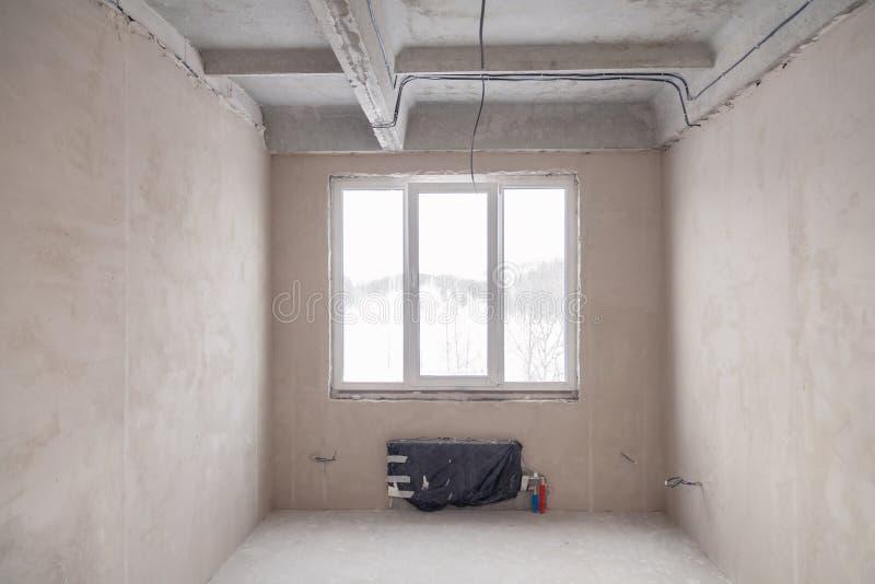 Tomt rum med ett f?nster och ett batteri i ett hus under konstruktion, packade v?ggar, en screed p? golvet, konkret flerniv?- arkivfoton