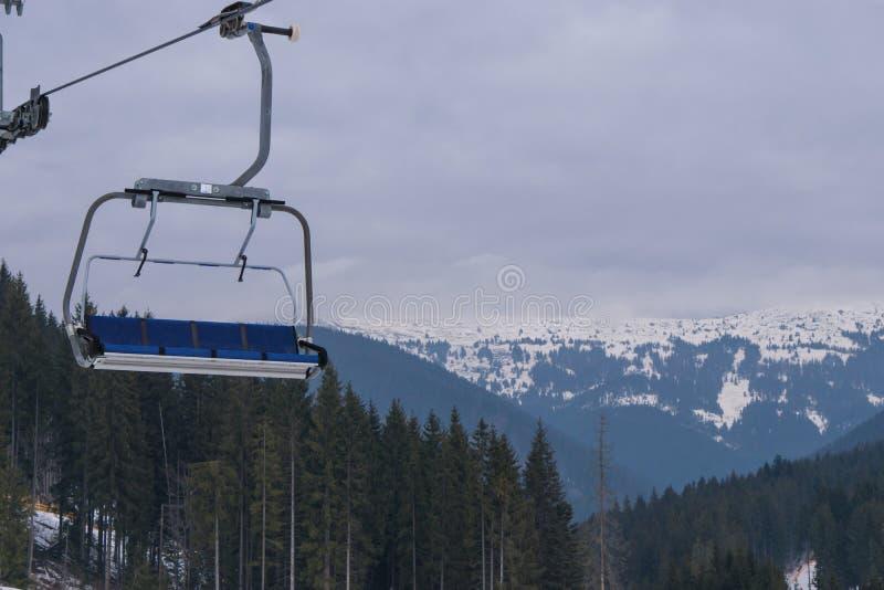 Tomt skidar chairliften med den härliga bergskogen på bakgrunden arkivfoton