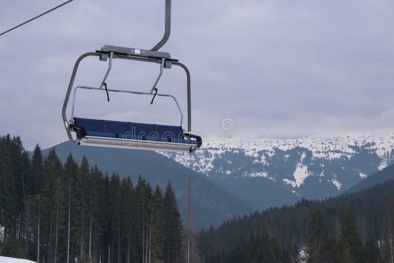Tomt skidar chairliften med den härliga bergskogen på bakgrunden royaltyfria bilder