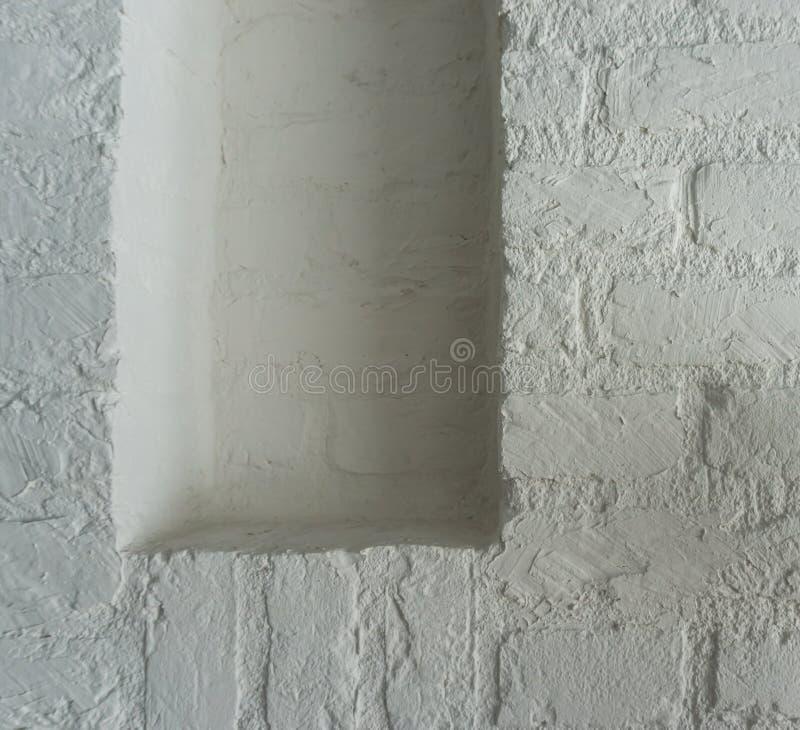Tomt stängt ramarbete i ett vitt utrymme för tegelstenvägg som tappar något som du gillar royaltyfri fotografi