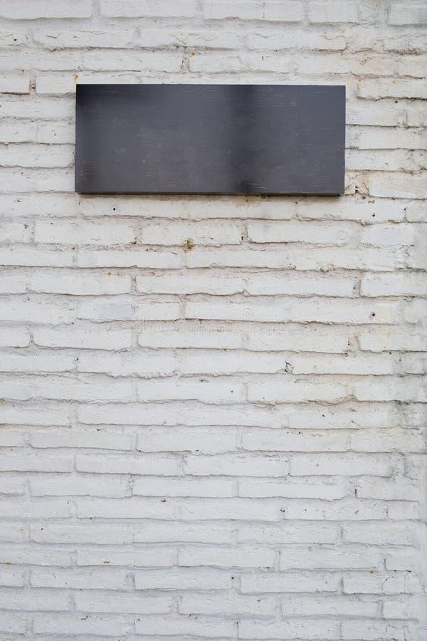 Tomt svart tecken som göras från marmorbräde på den vita tegelstenväggen royaltyfria foton