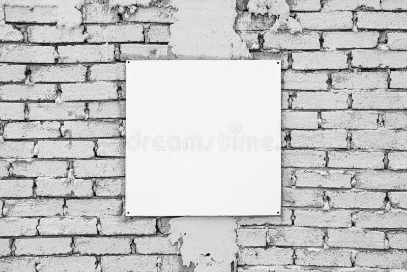 Tomt tecken på den vita tegelstenväggen Mallåtlöje upp royaltyfri fotografi