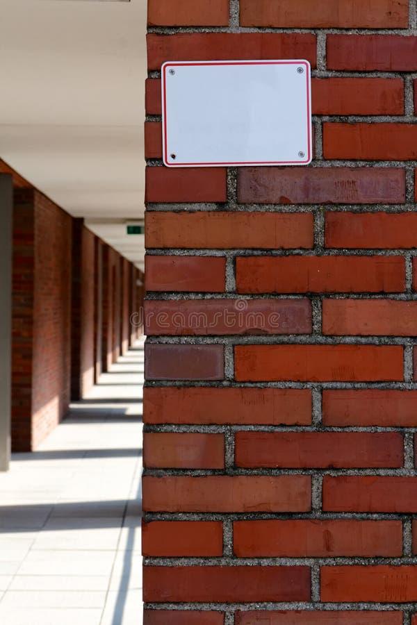 Tomt tecken på tegelstenväggen royaltyfri fotografi