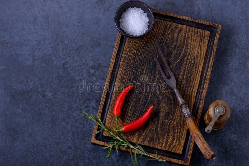Tomt träbräde för kött, gaffel, pepparshaker och örter och s arkivbild