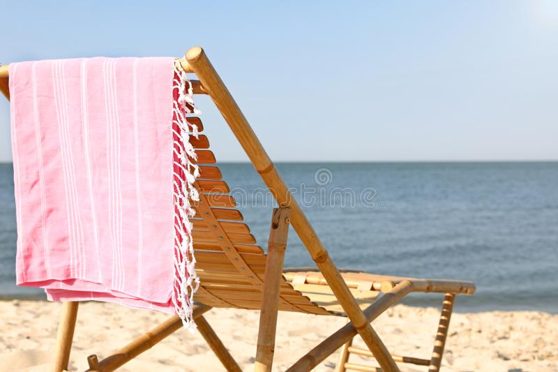 Tomt träsunbed och handduk på sandig kust arkivfoton