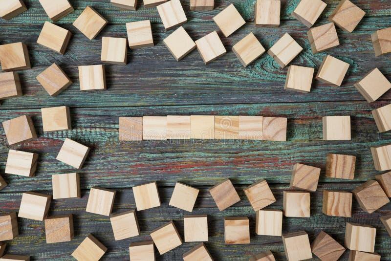 Tomt tr?kvarter som lutar p? en struktur som g?ras av m?nga andra texturerade kvarter med flera av dem fortfarande spritt ligga p arkivfoton