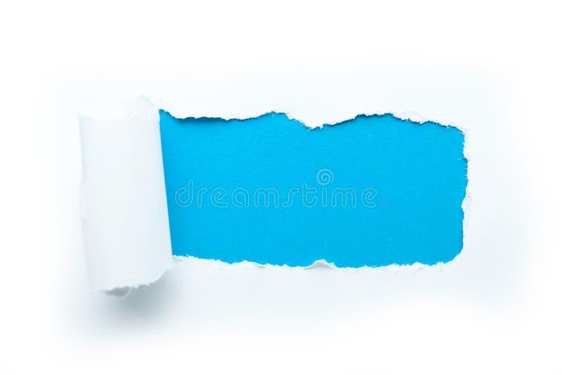Tomt utrymme f?r text p? en bl? bakgrund Ett sönderrivet av papper mot en vit bakgrund ?tl?je upp fotografering för bildbyråer