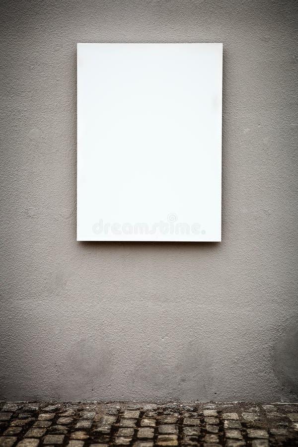 Tomt vertikalt vitt bräde på den Grungy väggen arkivbild