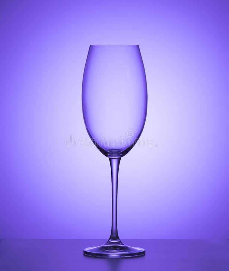 Tomt vinexponeringsglas på en purpurfärgad bakgrund close upp royaltyfria foton