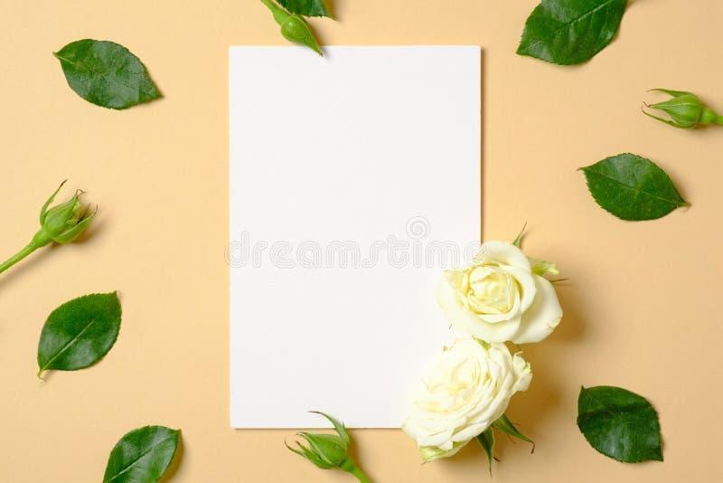 Tomt vitbokkort och ram som göras av rosblommor och gröna sidor på pastellfärgad gul bakgrund Bästa sikt, mjuk minsta lägenhet royaltyfri bild