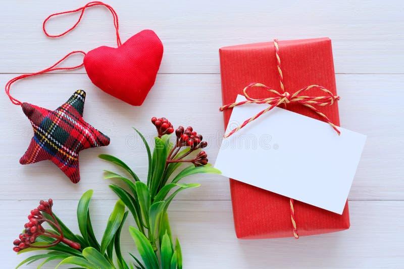 Tomt vitbokkort på den röda den tappninggåvaasken och prydnaden på vit träbakgrund, jul, nytt år, valentin dag och royaltyfria bilder