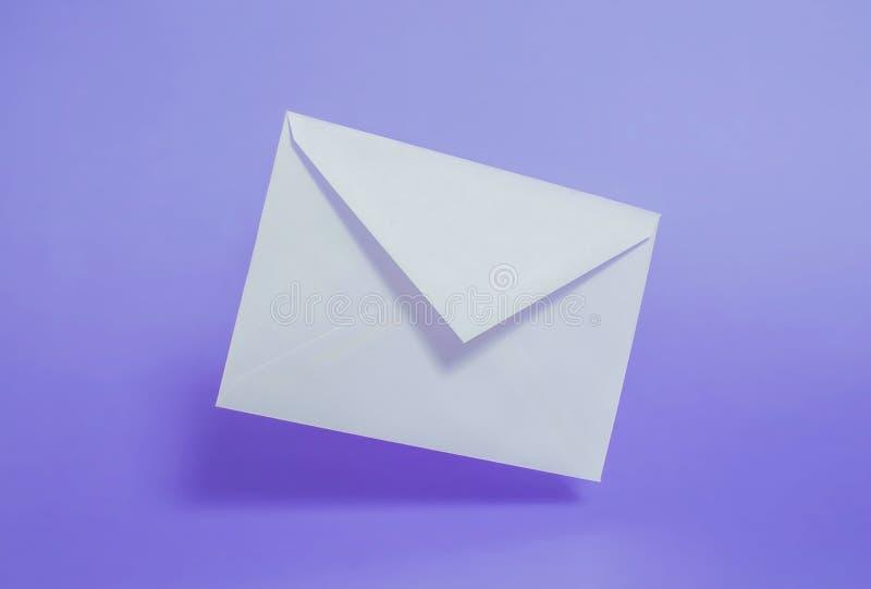 Tomt vitbokkuvert på en purpurfärgad bakgrund arkivbild