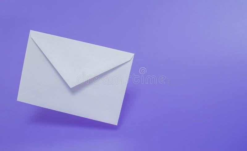 Tomt vitbokkuvert på enfärgad bakgrund arkivbilder