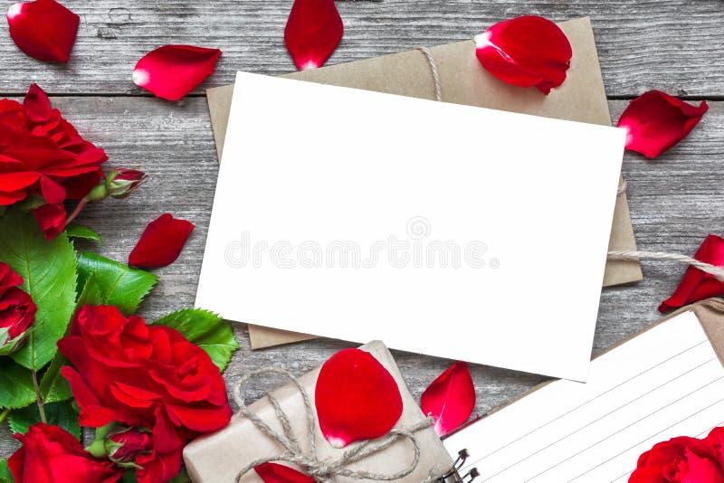 Tomt vitt hälsningkort med den röda rosblommabuketten och kuvert med kronblad, den fodrade anteckningsboken och gåvaasken arkivbilder