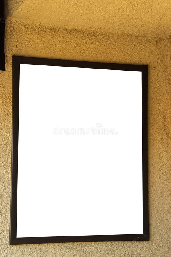 Tomt vittecken i brun ram på den guld- gula väggen arkivfoto
