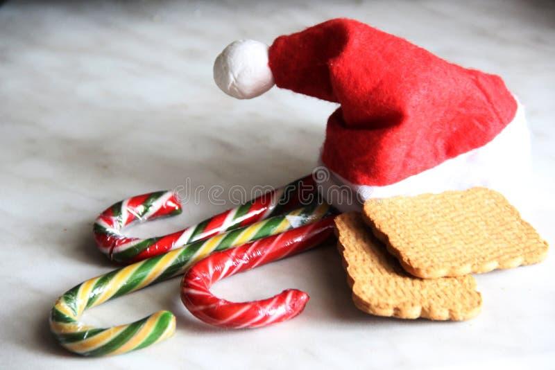 Tomtens röda hatt, tre kilo och två kortbröd Jul- och nyårssötsaker royaltyfria bilder