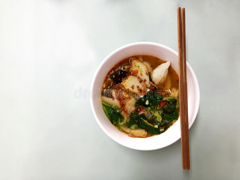 Tomyum fish noodle soup. Spicy tomyum fish noodle soup with lemongrass, chilly,lime juice and vegetables in bowl on the metal table.Thai noodles is delicious stock photography