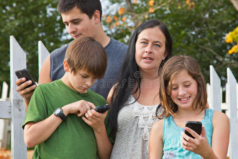 Tonår på mobiltelefoner arkivbild