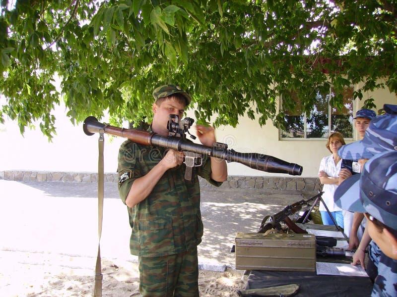 Tonåret visar moderna vapen i den ryska militärbasen fotografering för bildbyråer