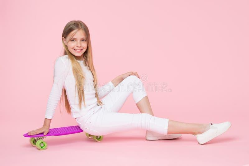 Tonårhobbybegrepp Flicka på att le framsidan som poserar med encentmyntbrädet, rosa bakgrund Flickan gillar för att rida skateboa royaltyfri foto